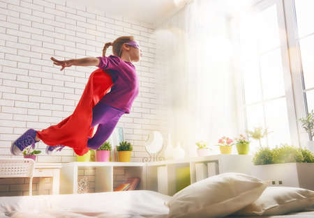 Child girl in Superhero's costume plays. The child having fun and jumping on the bed. Foto de archivo
