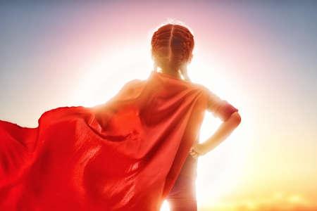 子供の小さな女の子は、スーパー ヒーローを果たしています。夕焼け空の背景の子。女の子パワー コンセプト