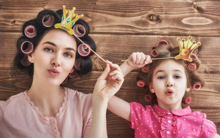 Funny family! Mother and her child daughter girl with a paper accessories. Beauty funny girl holding paper crown on stick. Beautiful young woman holding paper crown on stick. Stock Photo