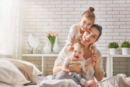madre: amante de la familia feliz. Madre y sus hijas niños niñas jugando y abrazos. Foto de archivo