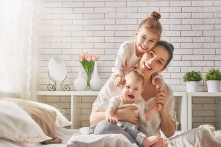caucasian: Happy loving family. Mother and her daughters children girls playing and hugging.