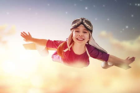 Little child girl plays astronaut. Child on the background of sunset sky. Child in an astronaut costume plays and dreams of becoming a spaceman. Stock Photo