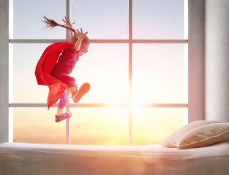 La muchacha del niño en obras de teatro del traje de super héroe. El niño que se divierten y saltar en la cama.