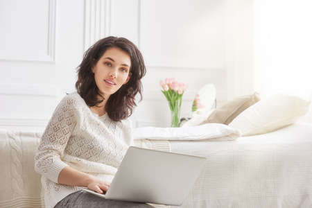 laptop home: Happy casual beautiful woman working on a laptop sitting on the bed in the house.