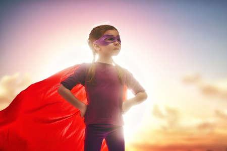 Weinig kind meisje speelt superheld. Kind op de achtergrond van avondrood. Girl power-concept Stockfoto