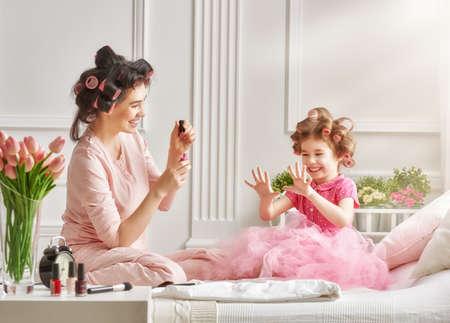 幸せな愛情のある家族。母と娘は、髪、マニキュア、楽しいことをやっています。母と娘の寝室のベッドの上に座っています。