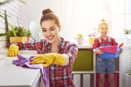 Glückliche Familie reinigt den Raum. Mutter und Tochter tun, um die Reinigung im Haus. Eine junge Frau und ein kleines Kind Mädchen Abstauben.
