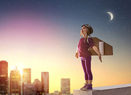 Little child girl plays astronaut. Child on the background of sunset sky. Child in an astronaut costume plays and dreams of becoming a spaceman. Archivio Fotografico