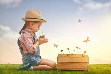Cute little child girl planting seedlings. Fun little gardener. Spring concept, nature and care. Stock Photo