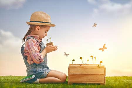 Cute little girl dziecko sadzonki sadzenia. Zabawna ogrodnikiem. Wiosna koncepcji, natura i opieki.