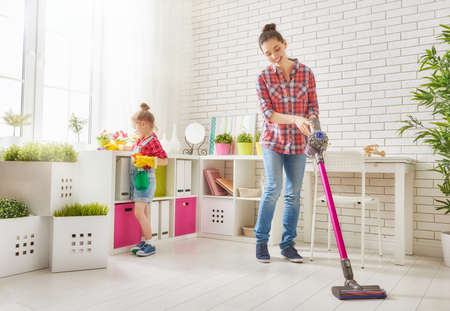 Šťastná rodina čistí prostor. Matka a dcera dělat úklid v domě. Mladá žena a malé dítě dívka setřel prach a vysát podlahu.