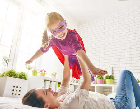 Mother and her child girl playing together. Girl in an Superheros costume. The child having fun and jumping on the bed.