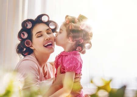 Feliz familia amorosa. Madre e hija se peinan y se divierten. Madre y su niña niño jugando, besándose y abrazándose.