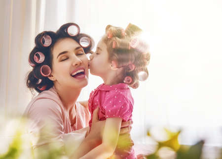 mother: Happy loving family. Mother and daughter are doing hair and having fun. Mother and her child girl playing, kissing and hugging. Stock Photo