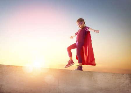 Kleines Kind Mädchen spielt Superheld. Kind auf dem Hintergrund der Sonnenuntergang Himmel. Mädchen Power-Konzept Standard-Bild - 54018568