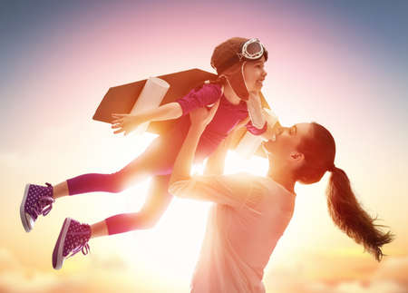 lady fly: Mother and her child playing together. Little child girl plays astronaut. Child in an astronaut costume plays and dreams of becoming a spaceman. Happy loving family having fun.