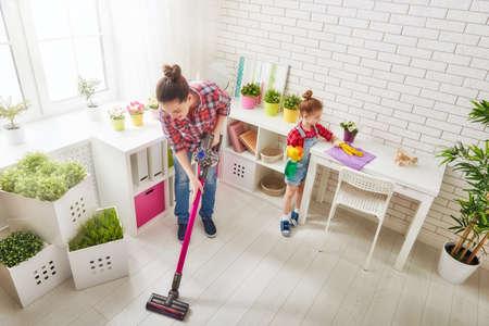 Familia feliz que limpia la habitación. Madre e hija hacen la limpieza de la casa. Una mujer joven y una muchacha del pequeño niño se limpió el polvo y aspirar el suelo.