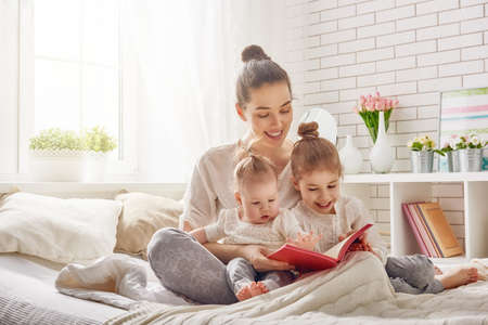 family at home: happy loving family. pretty young mother reading a book to her daughters