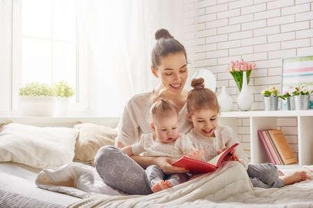 jeune fille: heureuse famille aimante. jolie jeune m�re lisant un livre � ses filles Banque d'images