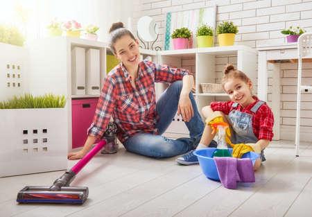 행복한 가족은 방을 정리합니다. 엄마와 딸이 집에서 청소를 할. 젊은 여자와 어린 아이 소녀는 먼지를 닦아 바닥을 진공 청소기로 청소.