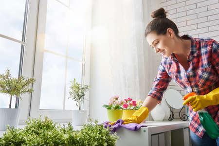 De mooie jonge vrouw maakt het schoonmaken van het huis. Meisje wrijft stof.