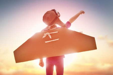 innovación: Niña niño juega astronauta. Niño en el fondo del cielo del atardecer. Niño en un traje de astronauta obras de teatro y sueños de convertirse en un hombre del espacio. Foto de archivo