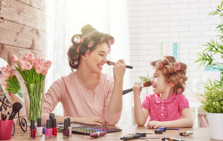 Happy loving family. Mother and daughter are doing hair, manicures, doing your makeup and having fun. Mother and daughter sitting at dressing table at house. Imagens