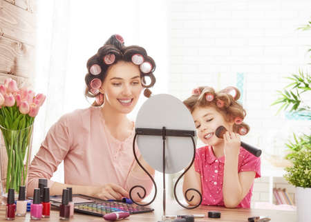 mommy: Happy loving family. Mother and daughter are doing hair, manicures, doing your makeup and having fun. Mother and daughter sitting at dressing table at house. Stock Photo