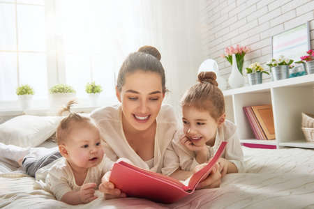 literatura: amante de la familia feliz. madre bastante joven que lee un libro a sus hijas