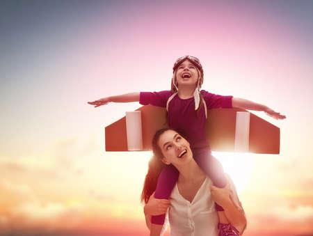 어머니와 그녀의 아이가 함께 연주. 작은 아이 소녀 우주 비행사을한다. 우주 비행사 의상 연극 우주인이되는 꿈에 자식입니다. 행복 한 사랑 가족 재