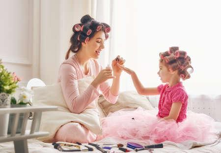 hija: amante de la familia feliz. La madre y la hija están haciendo para el cabello, manicura y divirtiéndose. Madre e hija sentada en la cama en el dormitorio. Foto de archivo