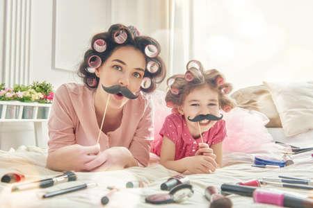 hija: Familia divertida! La madre y su hija niña niño con un accesorios de papel. La madre y la hija se prepara para una fiesta y la diversión. Joven y bella mujer y una niña divertida con un bigote de papel en el palillo.