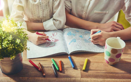 Bambino e adulto stanno dipingendo un libro da colorare. Nuovo lo stress tendenza alleviare. Concetto consapevolezza, il rilassamento.