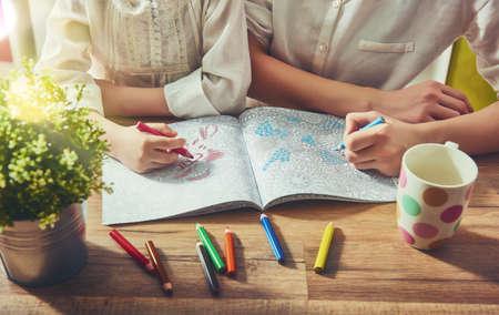 Crian�a e adulto est�o pintando um livro de colorir. aliviando a tend�ncia nova stress. Conceito mindfulness, relaxamento.