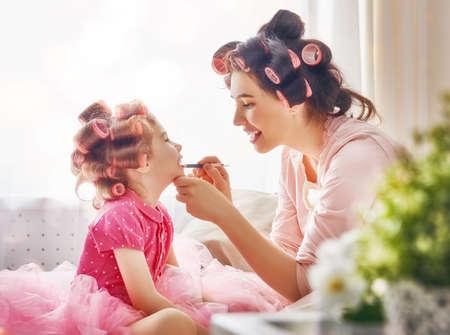 幸せな愛情のある家族。母と娘は髪を行うと楽しい時を過します。母は彼女の娘に口紅を置きます。