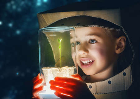 Child is dressed in an astronaut costume. Child sees a sprout in a glass case. The concept of environmental protection. Reklamní fotografie - 54018631