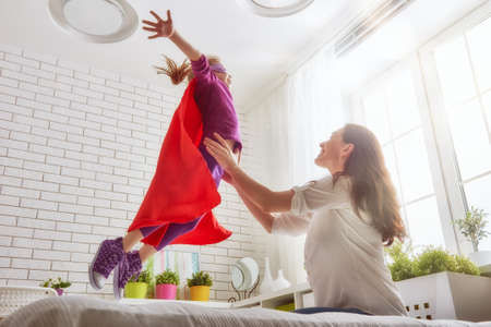 super power: Mother and her child girl playing together. Girl in an Superheros costume. The child having fun and jumping on the bed.