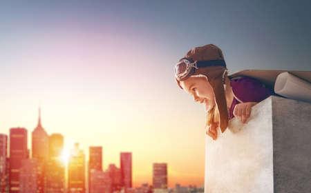 小さな子の女の子は、宇宙飛行士を果たしています。夕焼け空の背景の子。宇宙飛行士の子供衣装の演劇と宇宙飛行士になる夢。