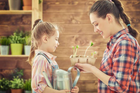 water plants: Cute child girl helps her mother to care for plants. Happy family engaged in gardening in the backyard. Mother and her daughter watering a growing sprout. Spring concept, nature and care. Stock Photo