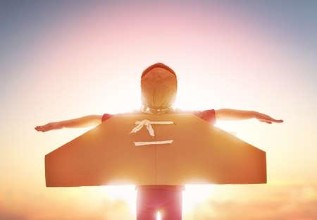 La bambina bambino gioca astronauta. Bambino sullo sfondo del cielo al tramonto. Bambino in un commedie di costume astronauta e sogna di diventare un astronauta.