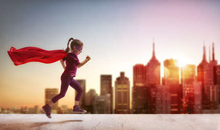 Dziewczynka dziecko bawi superbohatera. Dziecko na tle nieba słońca. Koncepcja girl power Zdjęcie Seryjne