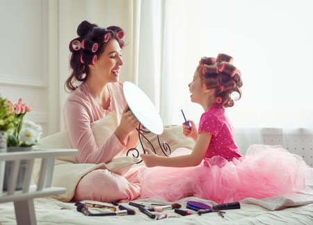 Happy loving family. Mother and daughter are doing hair and having fun. Mother and daughter doing your makeup sitting on the bed in the bedroom. 스톡 콘텐츠