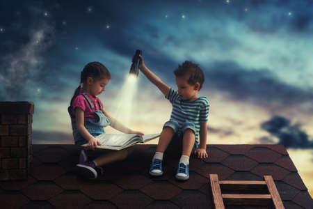 Niños leyendo un libro sentado en el techo de la casa. Niño y niña leyendo a la luz de una linterna en la noche. Foto de archivo