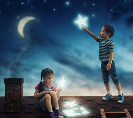 desire: Fairy tale! The children hung the stars in the sky. Boy and girl on the roof cut out stars.