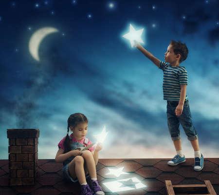 Sprookje! De kinderen hingen de sterren aan de hemel. Jongen en meisje op het dak uitgesneden sterren.
