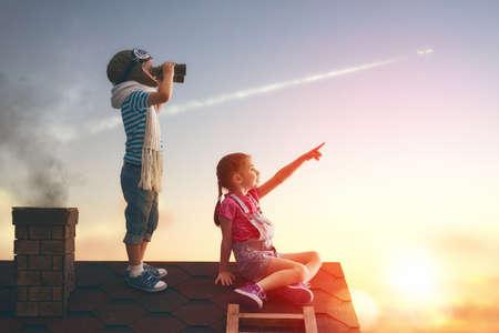 Twee kleine kinderen spelen op het dak van het huis en kijken naar de hemel en dromen ervan om een piloten.