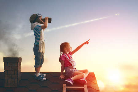 Two little children playing on the roof of the house and looking at the sky and dreaming of becoming a pilots. 版權商用圖片 - 54722902