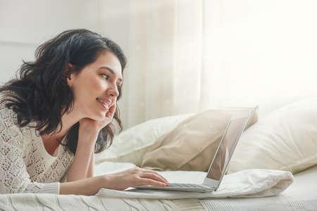 Felice bella donna casual che lavora su un computer portatile seduto sul letto in casa.