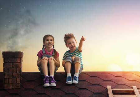 Dos niños lindos que se sientan en el techo y miran a las estrellas. Niño y niña pide un deseo al ver una estrella fugaz. Foto de archivo