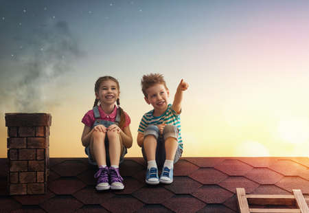 Two cute children sit on the roof and look at the stars. Boy and girl make a wish by seeing a shooting star. Фото со стока